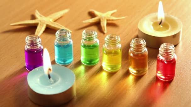 Paire d'étoiles de mer, deux cierges brûle, et six bouteilles ouvertes transparents stand en ligne sur la surface en bois avec de l'huile de couleur sur eux — Vidéo
