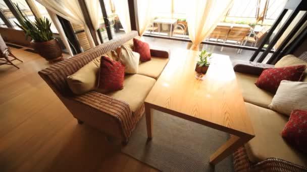 Sofás de mimbre soporte en restaurante lounge cercado de terraza por puerta de cristal — Vídeo de stock