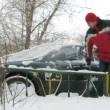 Stock Video: Min red jacket cleans car from snow