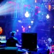 Stock Video: People in night club with illumination, dj on workplace