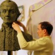 Stock Video: Sculptor Denis Petrov makes mold A.Suvorov bust of clay inside studio