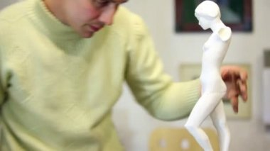 Sculptor polishes female figurine legs by file and look on it — Stock Video