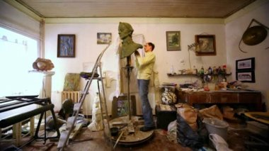 Sculptor Denis Petrov makes A.Suvorov bust among bugs, pail and other stuff lay around in studio — Stock Video
