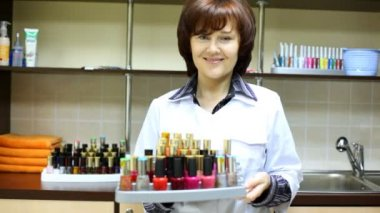 Woman-cosmetician represents nail polishes — Stock Video #30716561