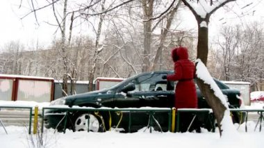 Woman cleans car from snow and pushes it that he went — Stock Video