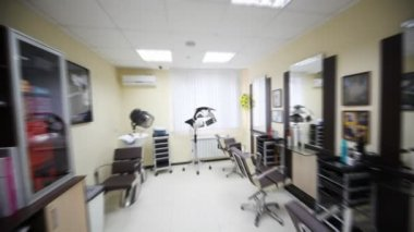 Flying motion of camera in hairdressing salon along armchairs to window — Stock Video
