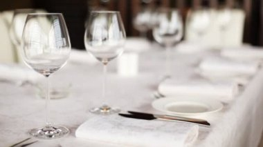Plates, knifes and wineglasses for wine stand on table covered with white cloth