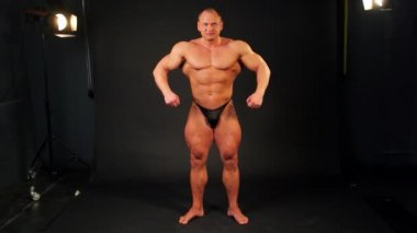 Bodybuilder shows his muscular body from behind and then turn around in studio — Stock Video