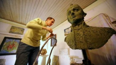 Sculptor Denis Petrov stands on stepladder and puts pieces of clay on unfinished A.Suvorov bust — Stock Video