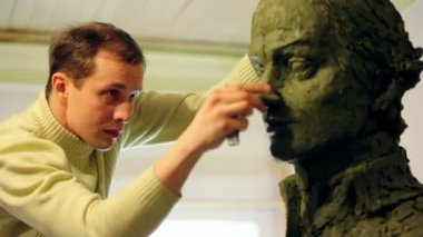 Sculptor Denis Petrov puts pieces of clay on nose of unfinished A.Suvorov bust and watch on it — Stock Video