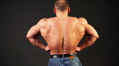 Bodybuilder shows his muscular body from behind and then turn around lit — Stock Video