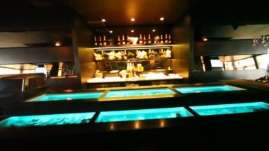 Aquariums with oysters are built in bar counter and on showcase there is champagne in oyster bar — Stockvideo