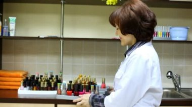 Woman-cosmetician represents nail polishes — Stock Video