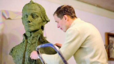 Sculptor Denis Petrov puts pieces of clay on unfinished A.Suvorov bust — Stock Video