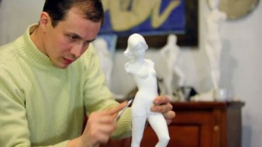 Sculptor polishes female figurine by file at background of other statuettes — Stock Video