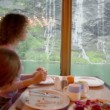Woman with her kids sit at table and eat in front of window — Stock Video