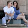 Stock Video: Young couple sit on steps near colonnade, fluff flies around