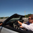 Young couple ride in cabriolet by road at sunny summer day — Stock Video