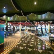 Few people walk in empty casino with play machines around — Vídeo de stock