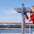Stock Video: Boy looks in binocular on ship deck against blue sky