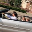 Belt up family ride in cabriolet near huge architectural complex — Stock Video