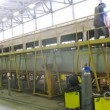 Stock Video: Welder welds roof on carriage in assembly shop of plant