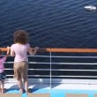 Mother and daughter stand on deck of ship looking at boat — 图库视频影像