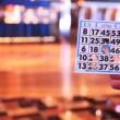 Hand holds ticket for game in bingo and leader declares figures — Stock Video #32342069
