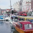 Stock Video: Boats are in dock of coastal town Bergen, tourists walk around