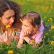 Mother and daughter lie on lawn with flowers in hair — Vídeo Stock