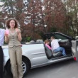 Parents eat near cabriolet and their kids play in car — Stock Video