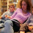 Mother with two her kids sit on sofa and read book in small room — Stock Video