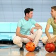 Two students sit and spin balls at background of bowling lane — Stock Video #32342479