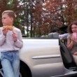 Boy stand and eats near cabriolet, his parents drink in car — Stock Video