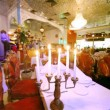 Lounge of restaurant is located behind candlestick with candles — Stock Video