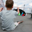 Boy sit on roof and hold shroud lines, parachute inflated by air — Stock Video #32343269