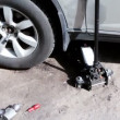 Lifting jack under car, few tools lie near, shown in motion — Vídeo Stock