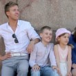 Stockvideo: Young couple and pair of little kids stand near column