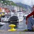 Stock Video: Womsits and sings on quay in dock at coastal Bergen town