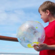 Stockvideo: Little boy stand near railing and hold inflated ball