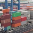 Lot of containers on board of barge and at shore of port — Stock Video #32344071