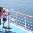 Stock Video: Girl looks in binocular on ship deck under direction of mother.