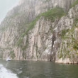 Stock Video: Touristic vessel floats by fiord near rocky cliff at fiord