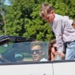 Couple with kids sit in cabriolet, boy wag finger at kids behind — Stock Video #32344377