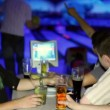Young man plays bowling and his friends drink beer in dark club — Stock Video