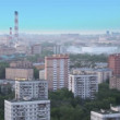 Stock Video: Panorama of city with houses among trees in fog at summer day