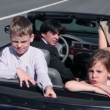 Parents and two kids seat in car and ride away at sunny day — Stock Video #32344765