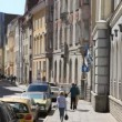 Stock Video: Street of old city with carriageway and sidewalk with flags