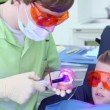 Stock Video: Dentist holds jaw and uses light for harden filling near boy
