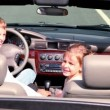 Parents and kids sit in cabriolet and look backward then turn — Vídeo Stock